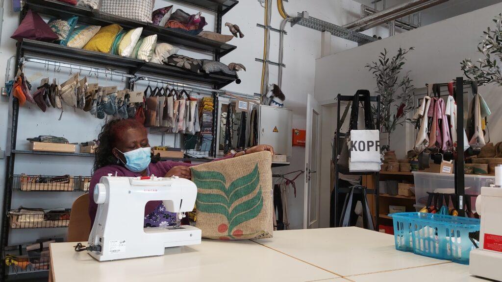 Eine Frau sitzt in einer Werkstätte und zeigt eine Upcycling-Tasche, die sie soeben genäht hat.